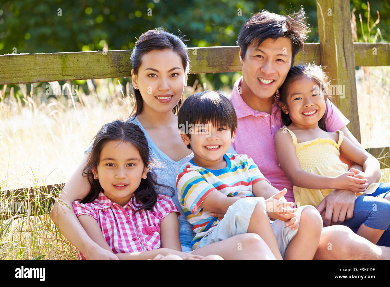 Asian Family Relaxing By Gate On Walk In Countryside - Stock Image