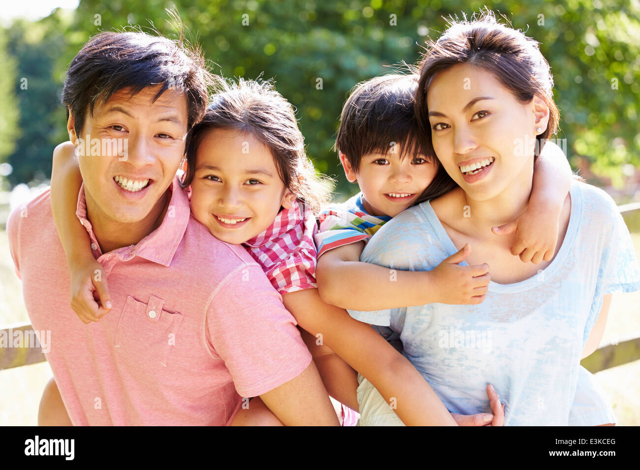 Portrait Of Asian Family Enjoying Walk In Summer Countryside - Stock Image