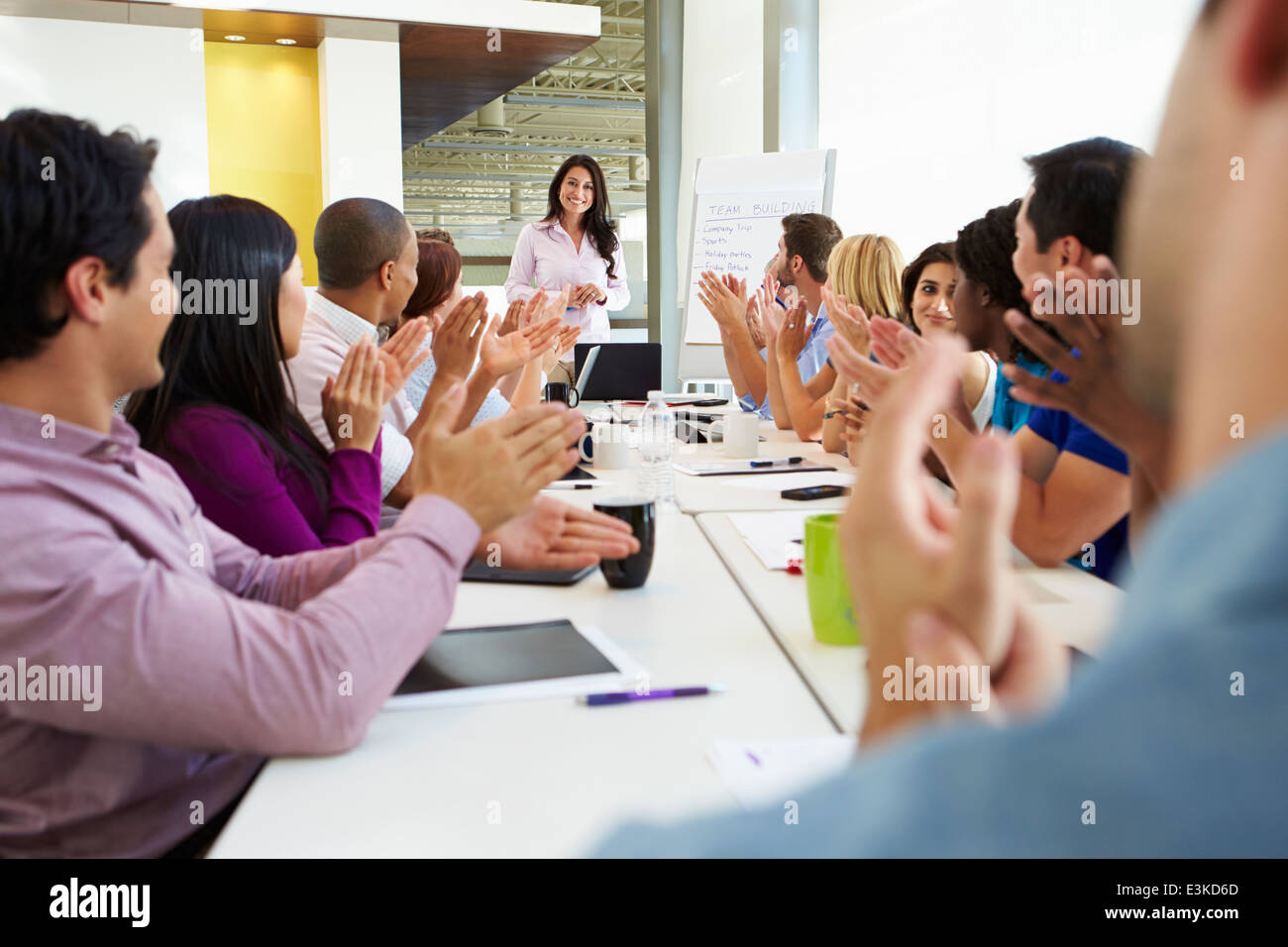 Businesswoman Addressing Meeting Around Boardroom Table - Stock Image