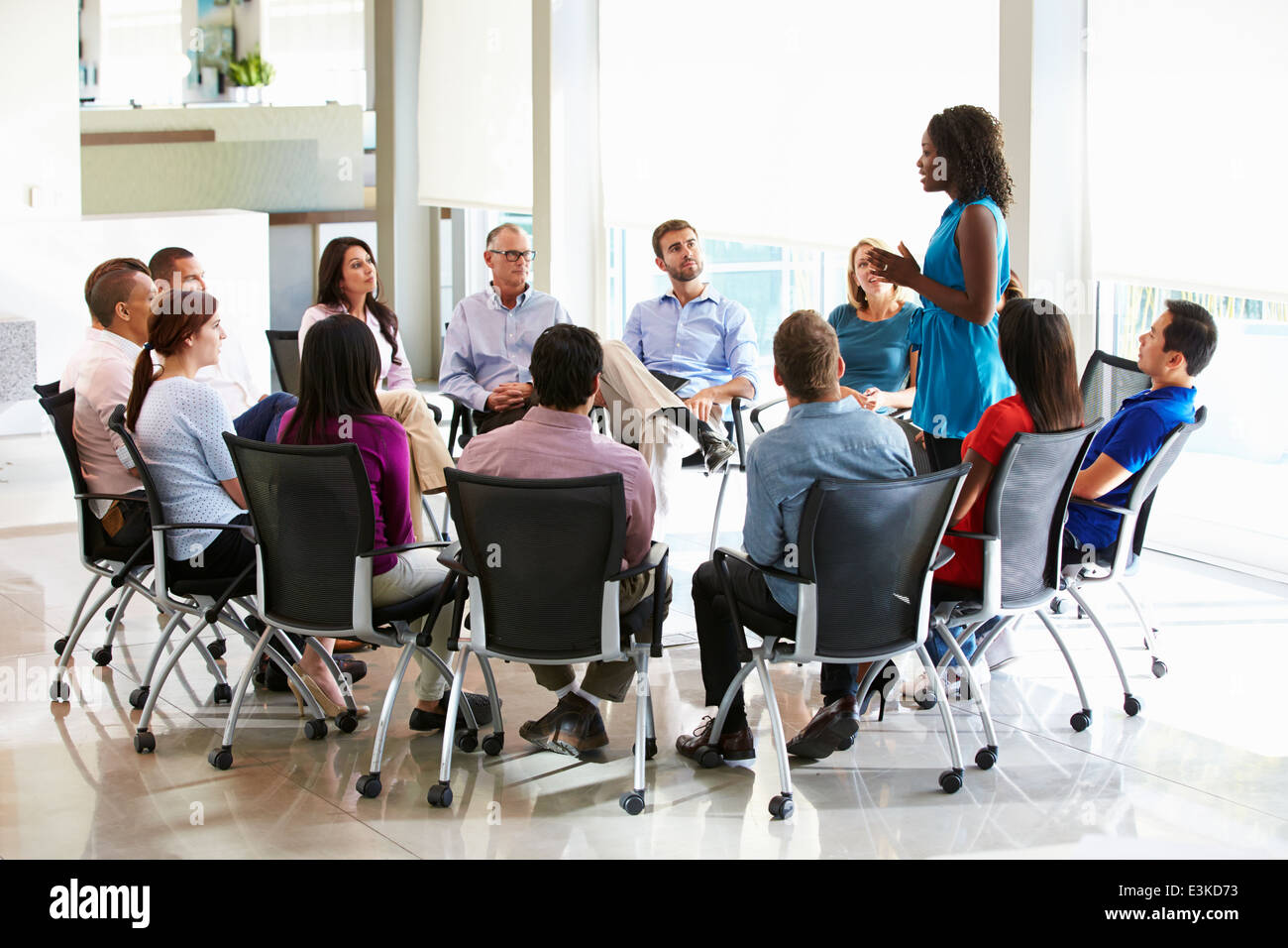 Businesswoman Addressing Multi-Cultural Office Staff Meeting - Stock Image