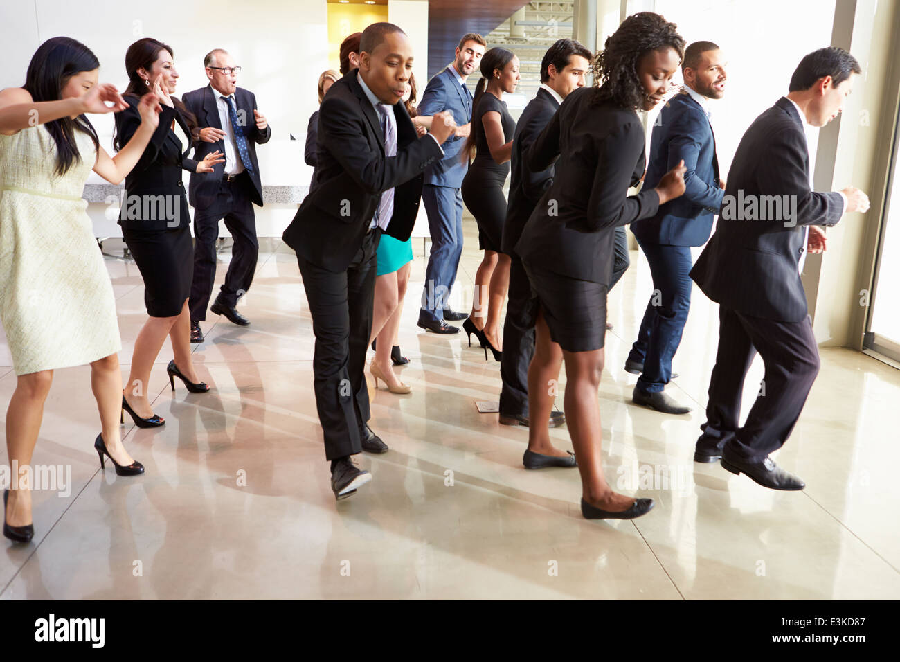 Businessmen And Businesswomen Dancing In Office Lobby - Stock Image