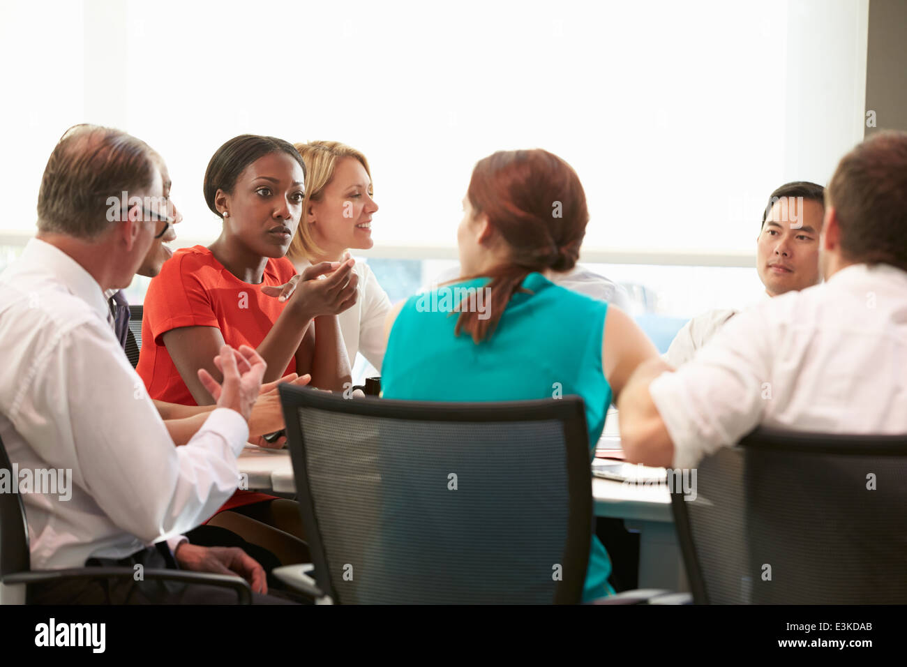 Group Of Businesspeople Meeting Around Boardroom Table - Stock Image