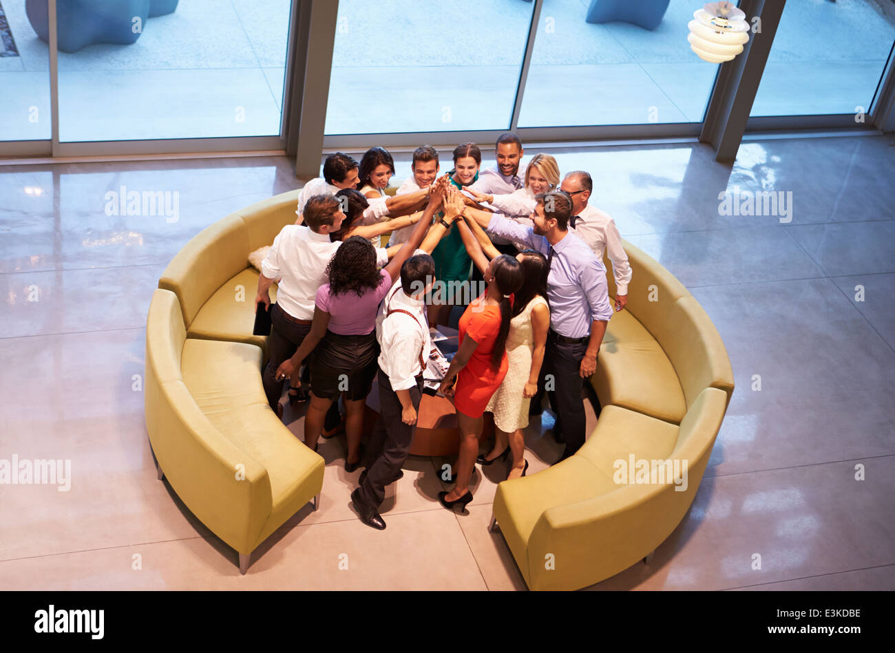 Businesspeople Giving Each Other High Five In Office Lobby - Stock Image