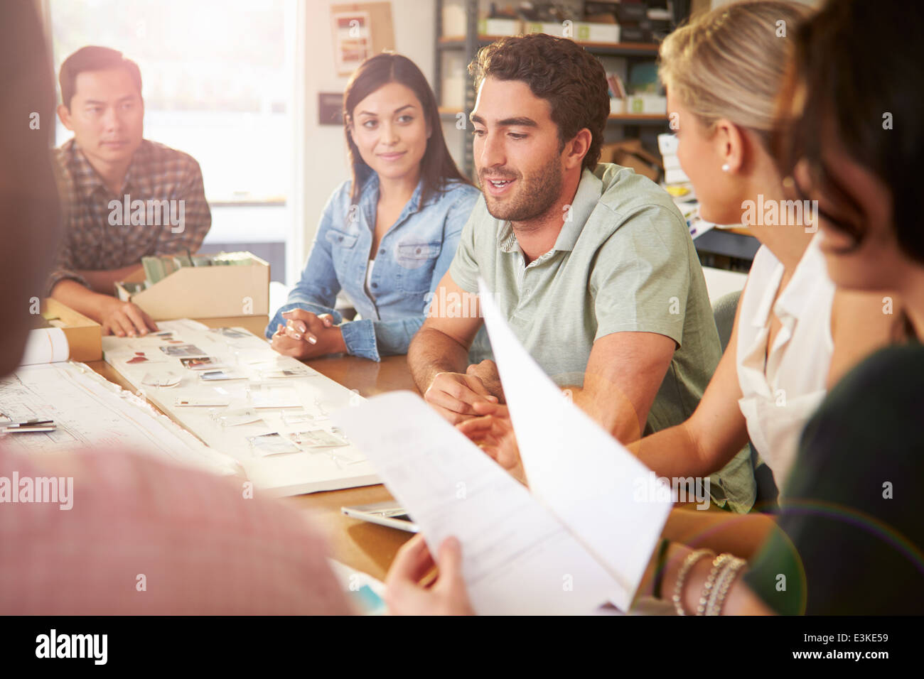 Six Architects Sitting Around Table Having Meeting - Stock Image