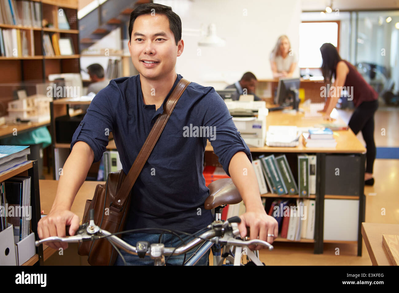 Architect Arrives At Work On Bike Pushing It Through Office - Stock Image