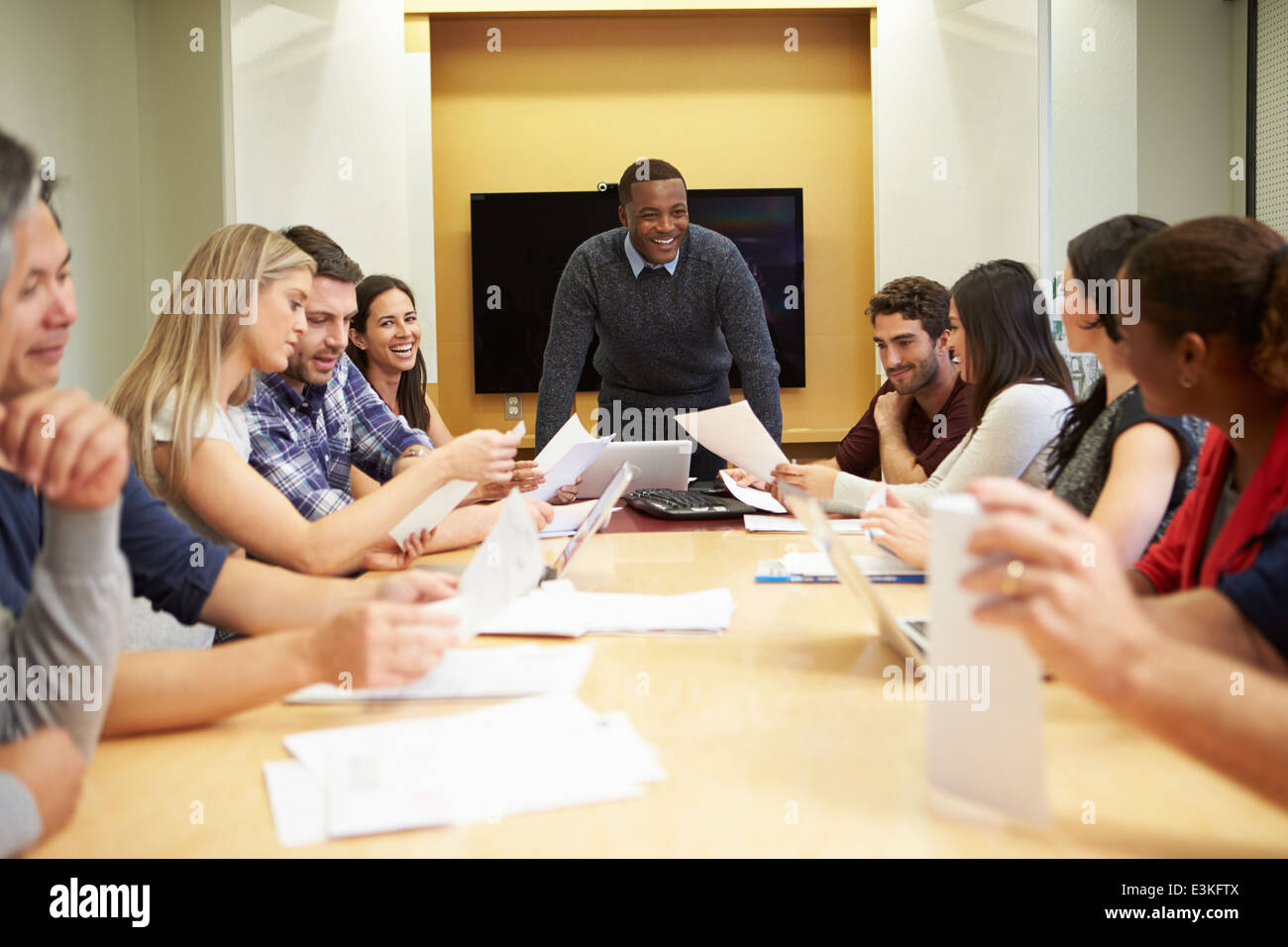 Male Boss Addressing Meeting Around Boardroom Table - Stock Image