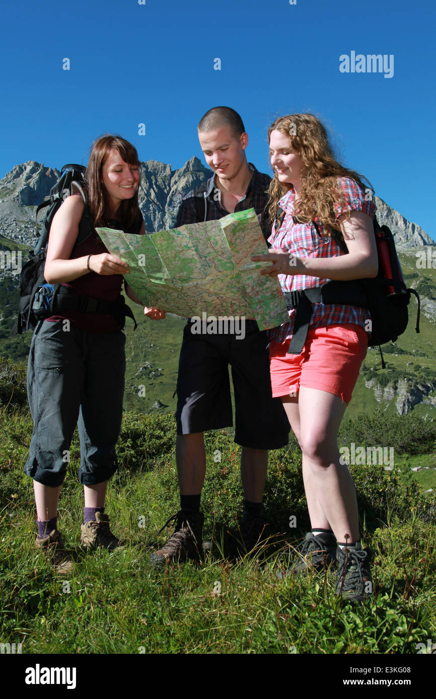 Young people reading a map for orientation in the mountains. - Stock Image