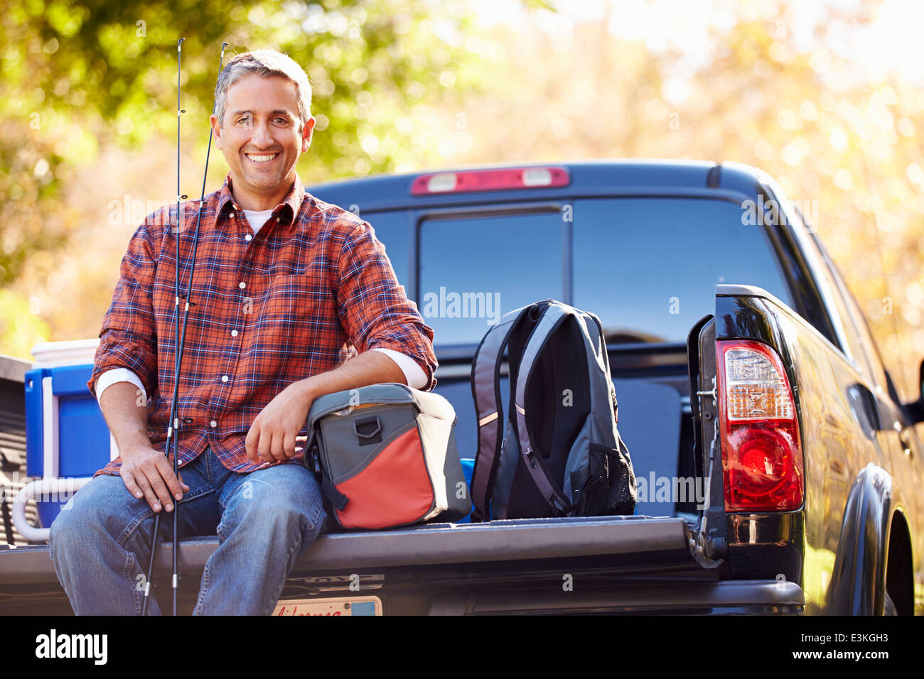 Portrait Of Man Sitting In Pick Up Truck On Camping Holiday - Stock Image
