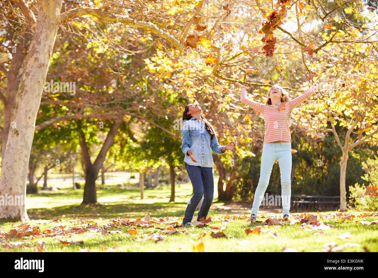 Two Girls Throwing Autumn Leaves In The Air - Stock Image