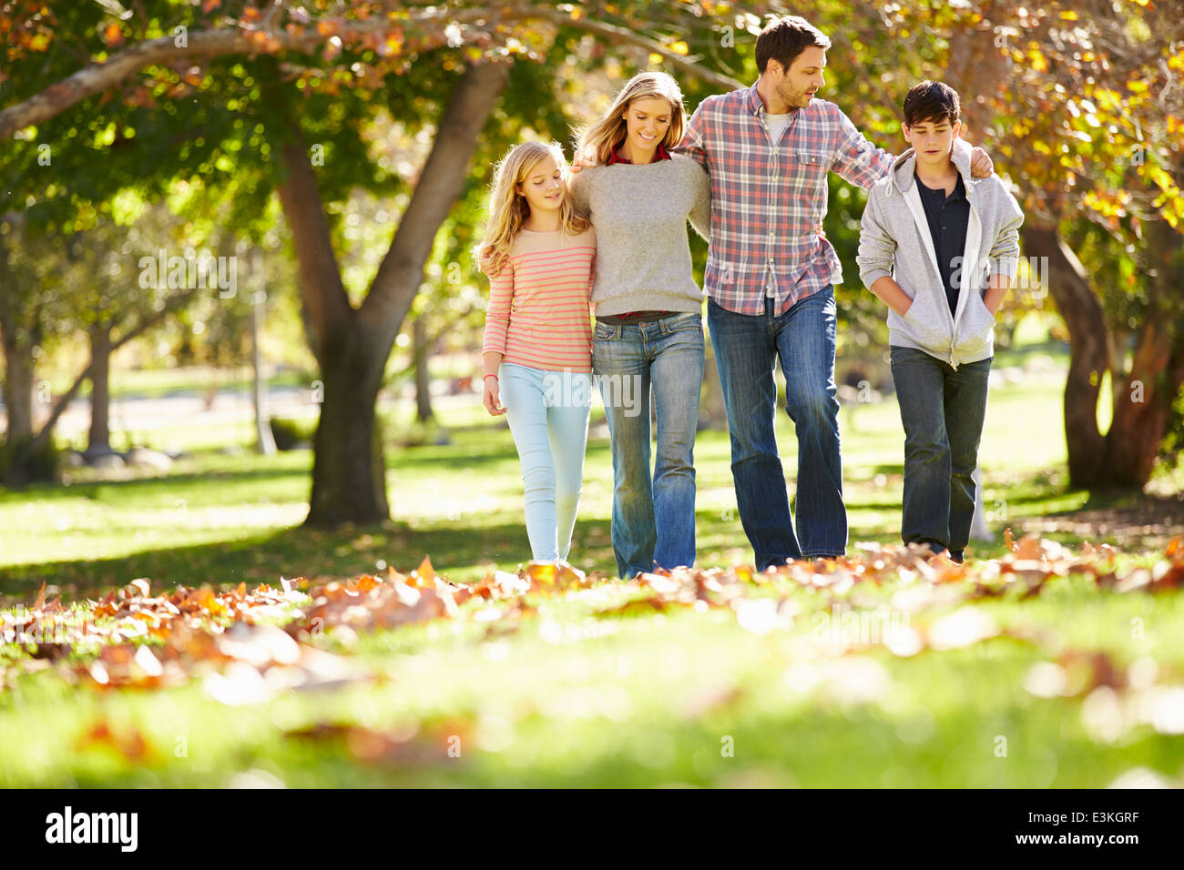 Family Walking Through Autumn Woodland - Stock Image