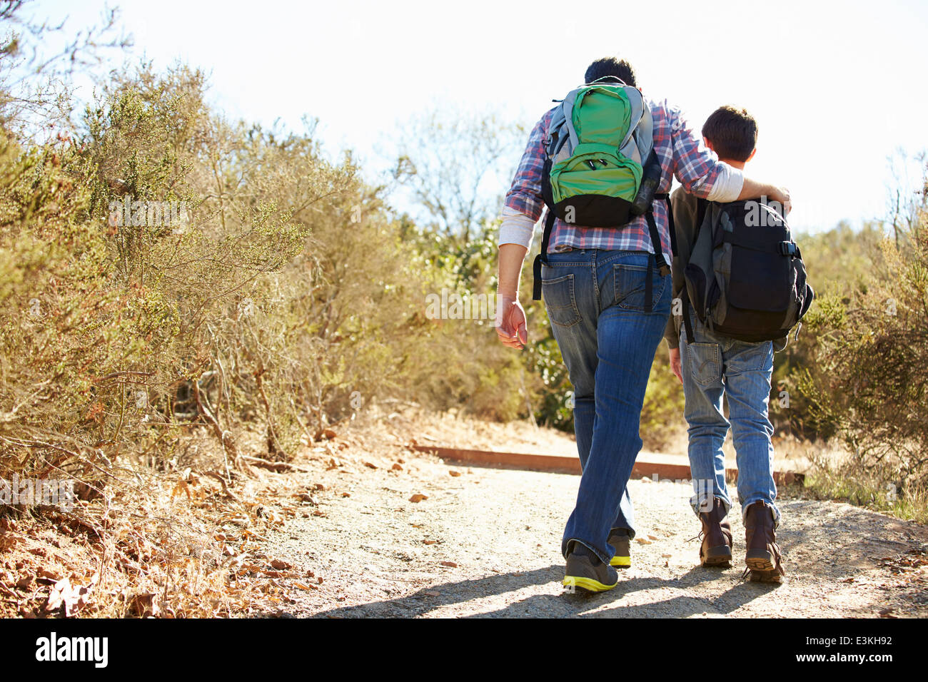 Rear View Of Father And Son Hiking In Countryside - Stock Image