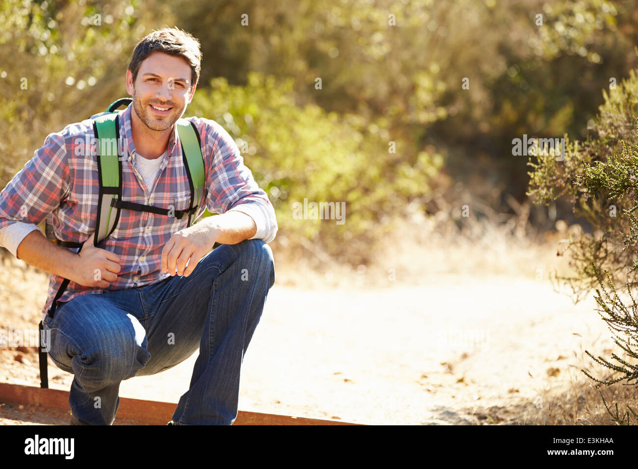 Portrait Of Man Hiking In Countryside Wearing Backpack - Stock Image