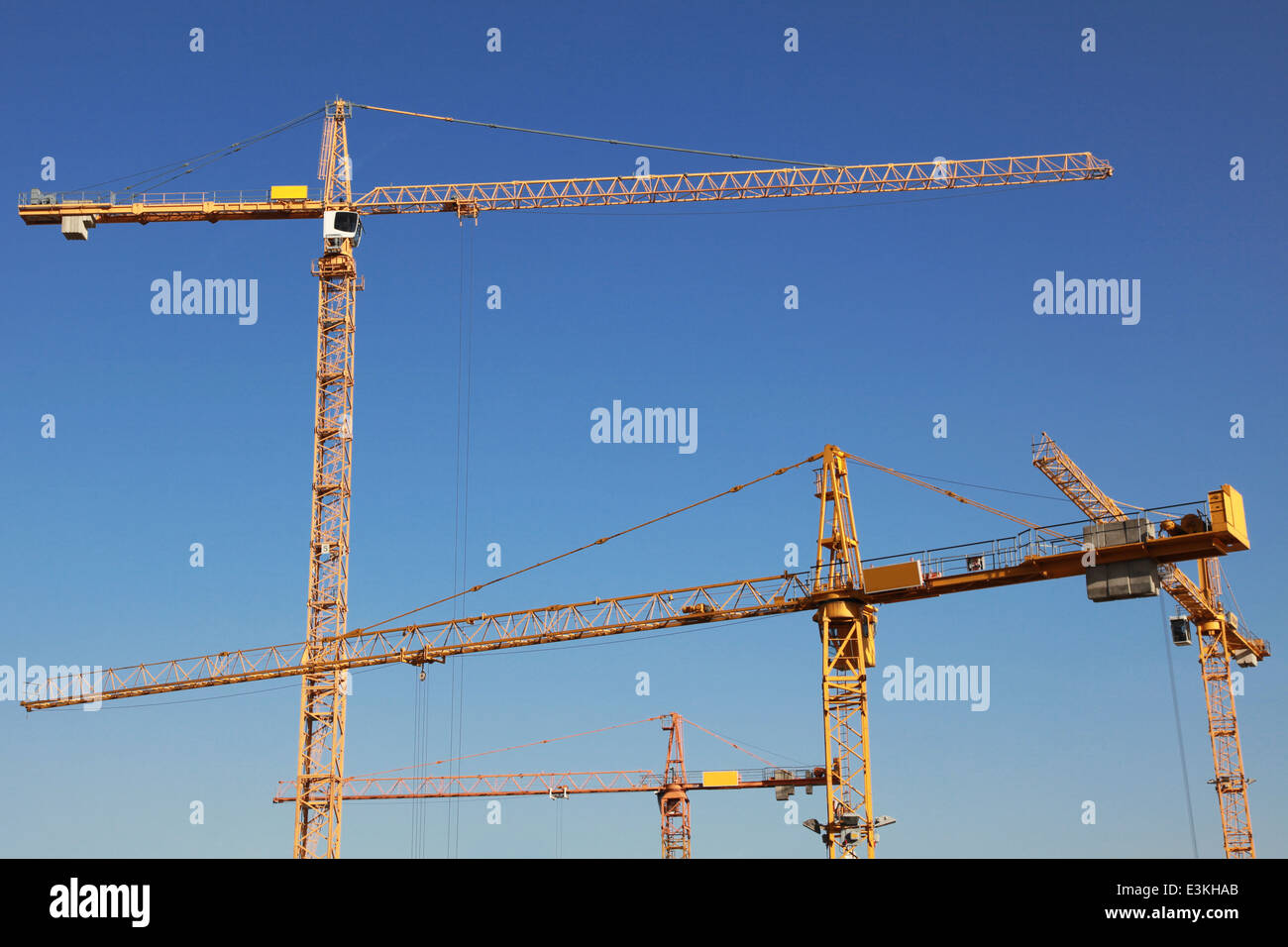 Several yellow tower cranes on a construction site - Stock Image