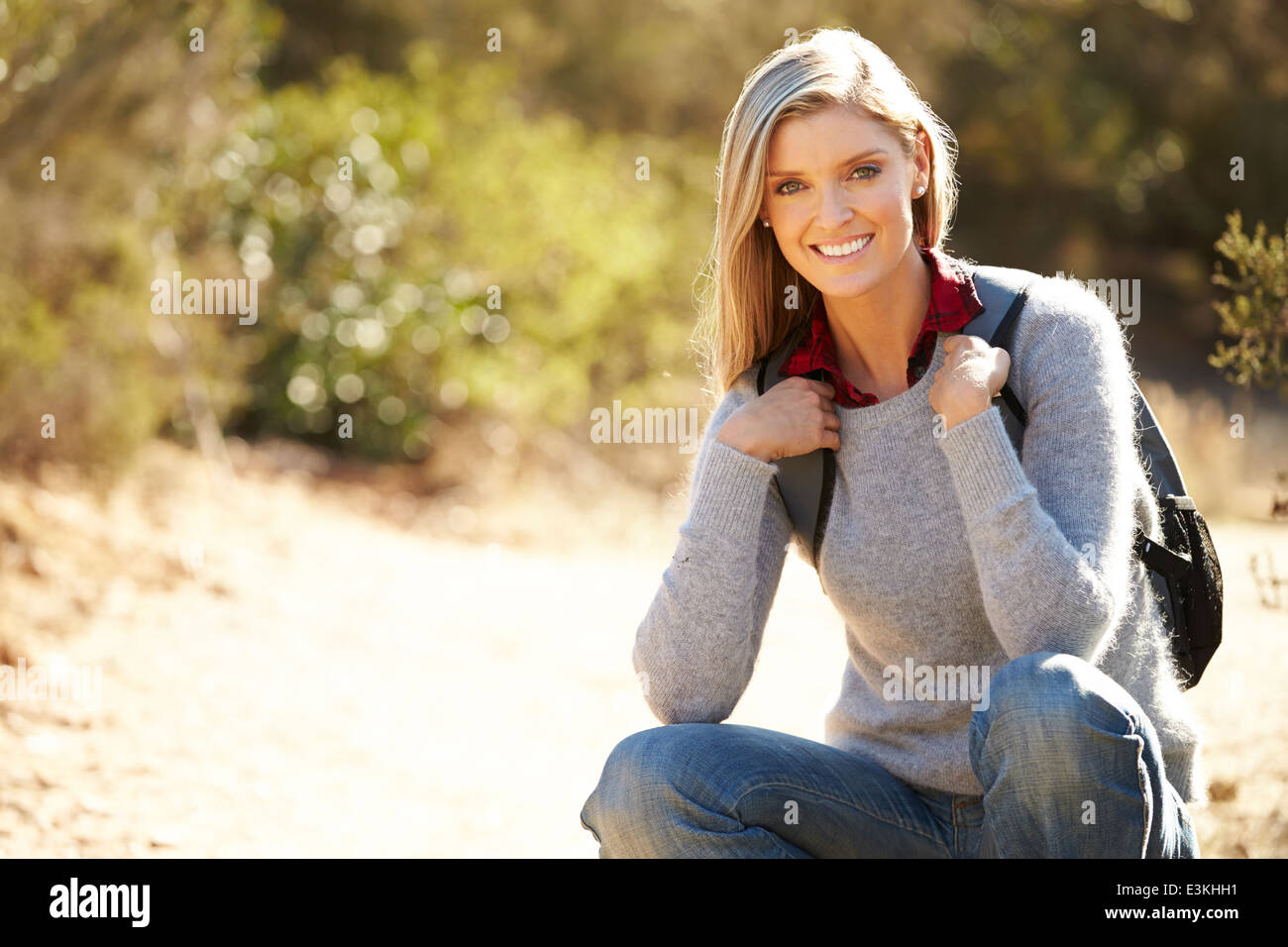 Portrait Of Woman Hiking In Countryside Wearing Backpack - Stock Image
