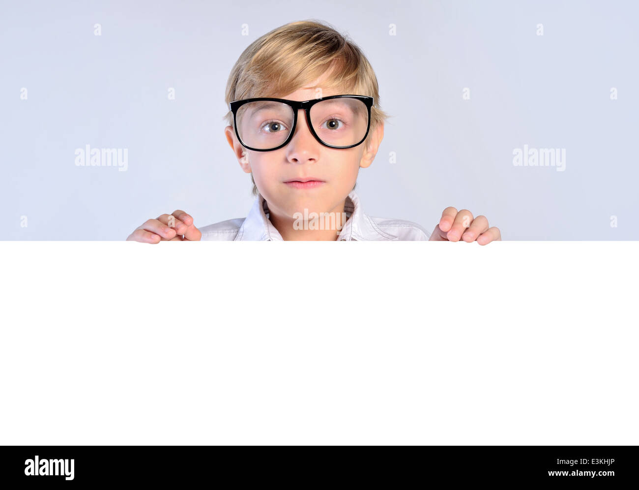 Young nerd boy leaning on blank banner - Stock Image