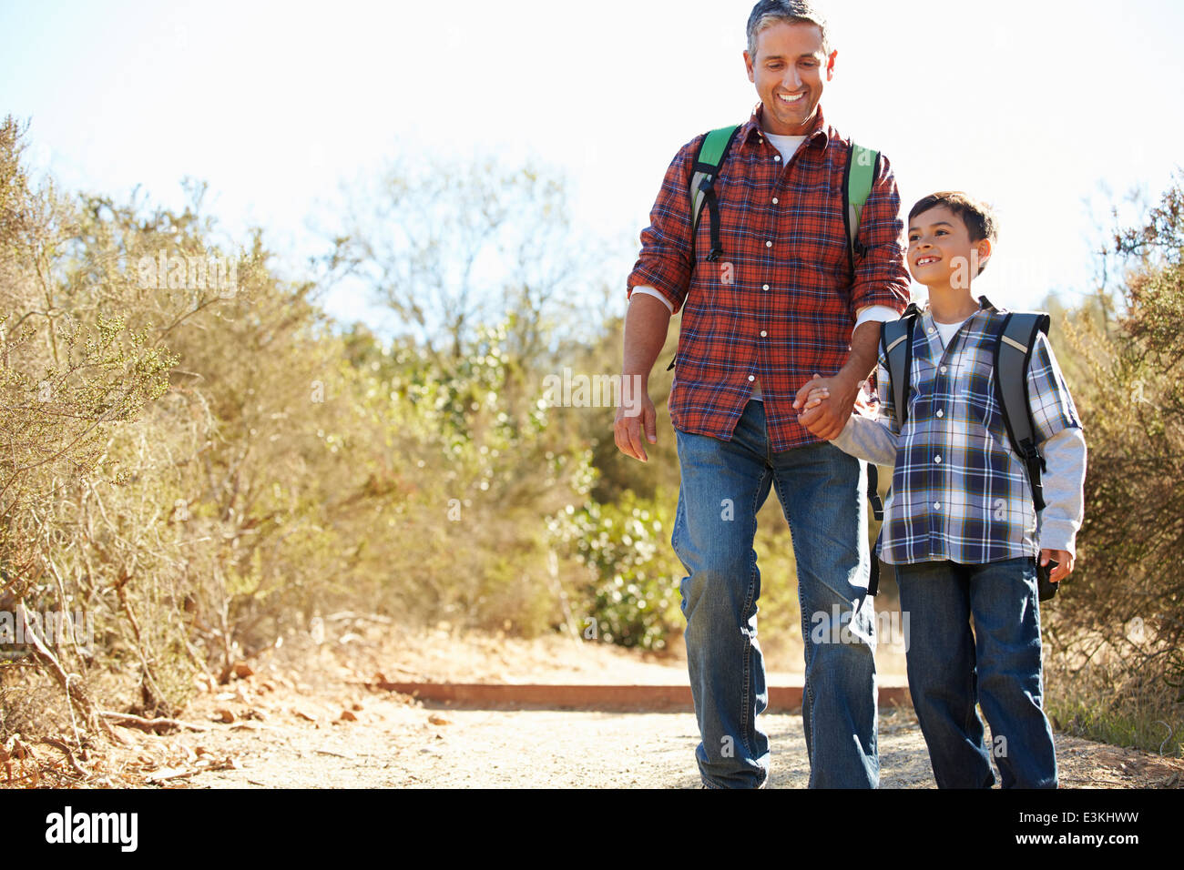 Father And Son Hiking In Countryside Wearing Backpacks - Stock Image