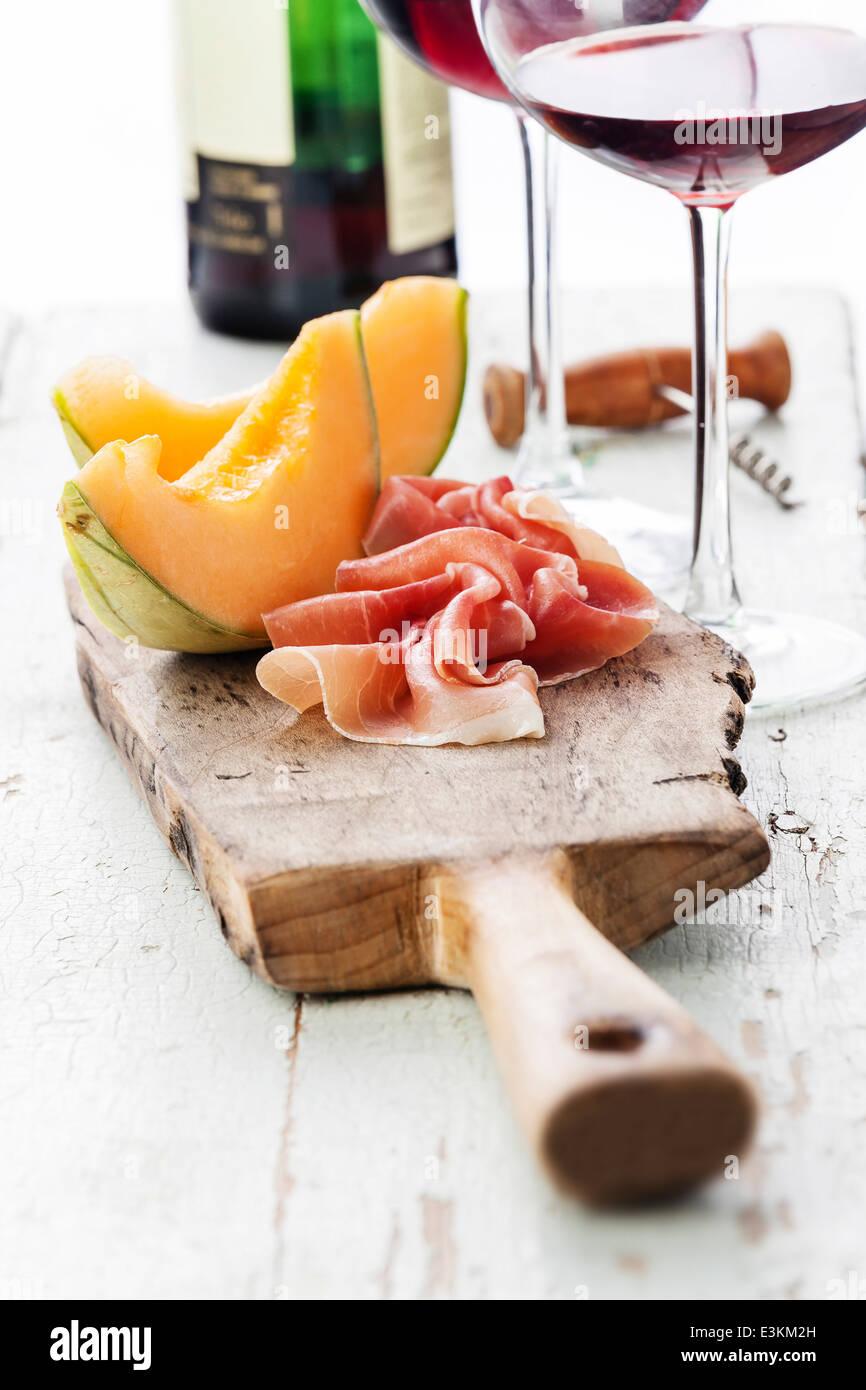 Slices of melon cantaloupe with prosciutto ham - Stock Image
