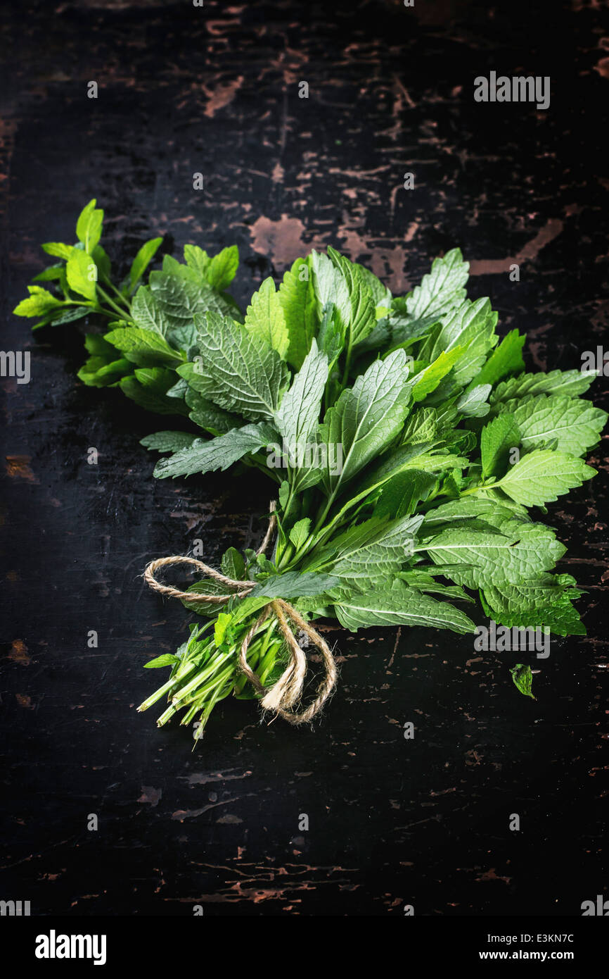 Bunch of fresh mint over black wooden table. Top view. - Stock Image