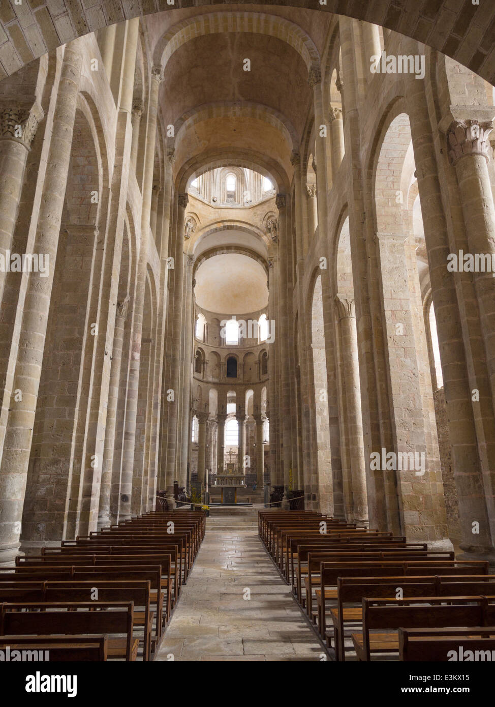 The austere interior centre aisle of the Church of Saint Foy . Columns soar and the plain interior stonework glows - Stock Image