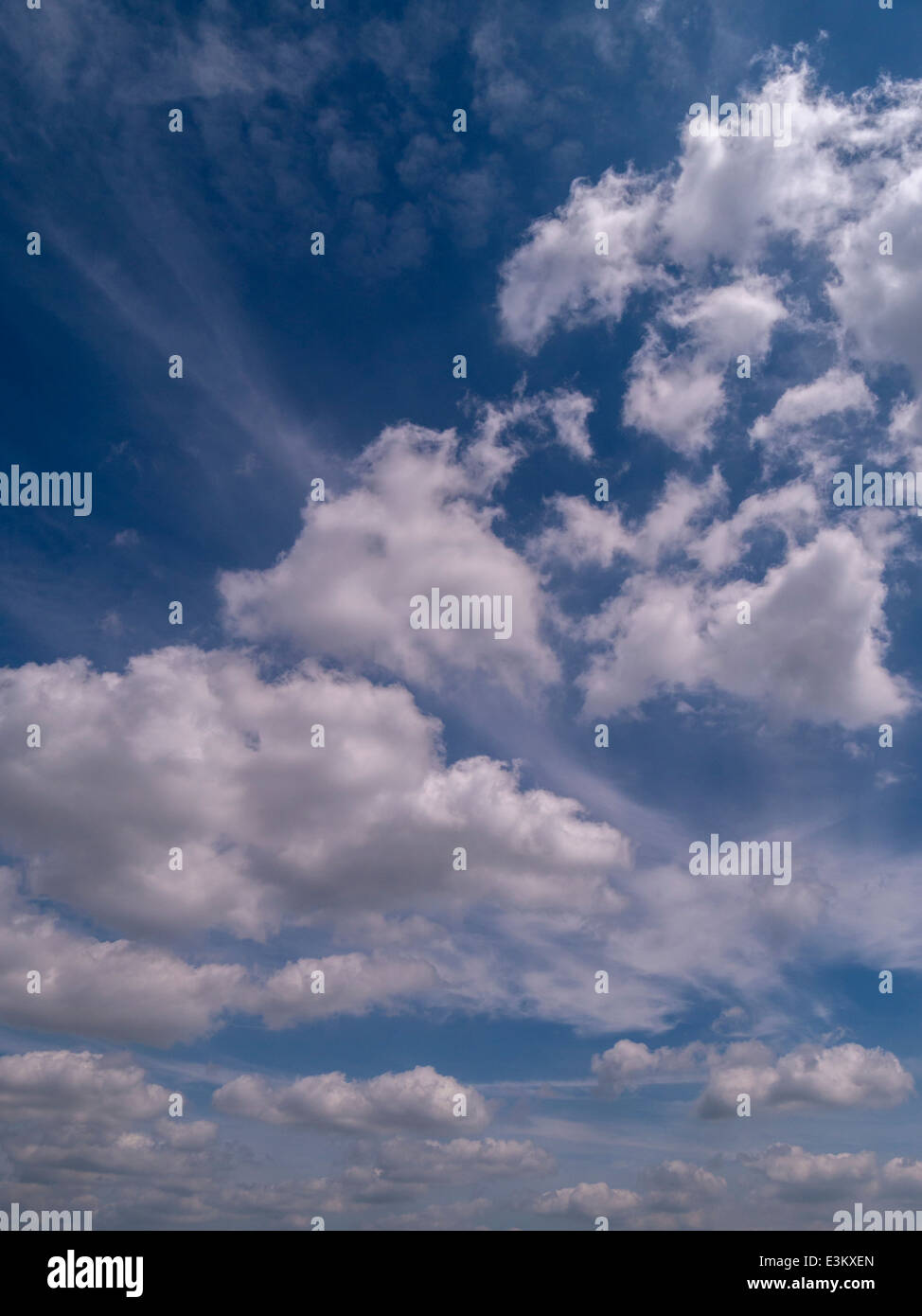 White cumulus clouds against deep blue sky with wispy high level cirrus clouds - Stock Image