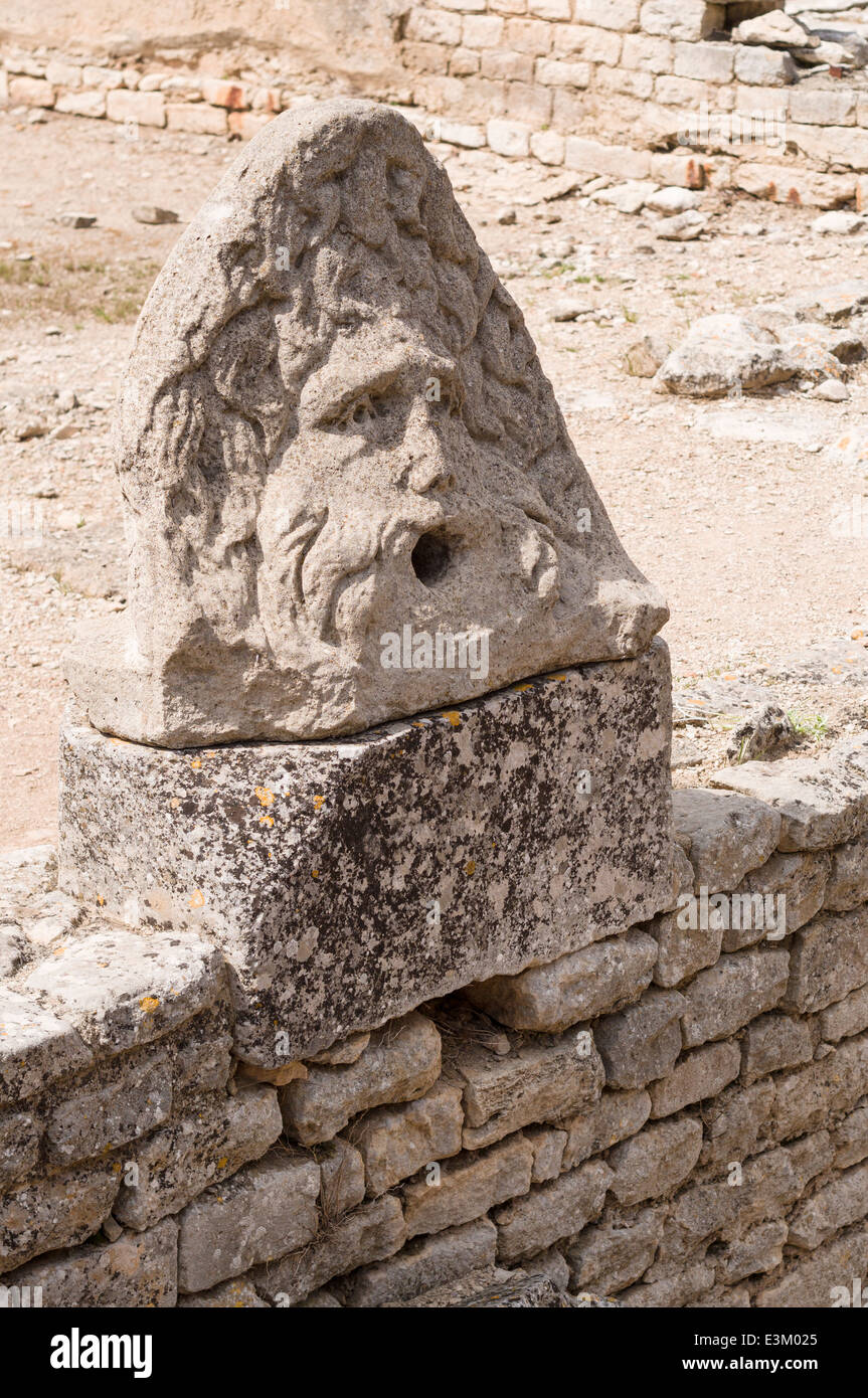 Carving rescued from the ruins of Glanum. Probably a fallen building ornament of a man's face, now placed on - Stock Image