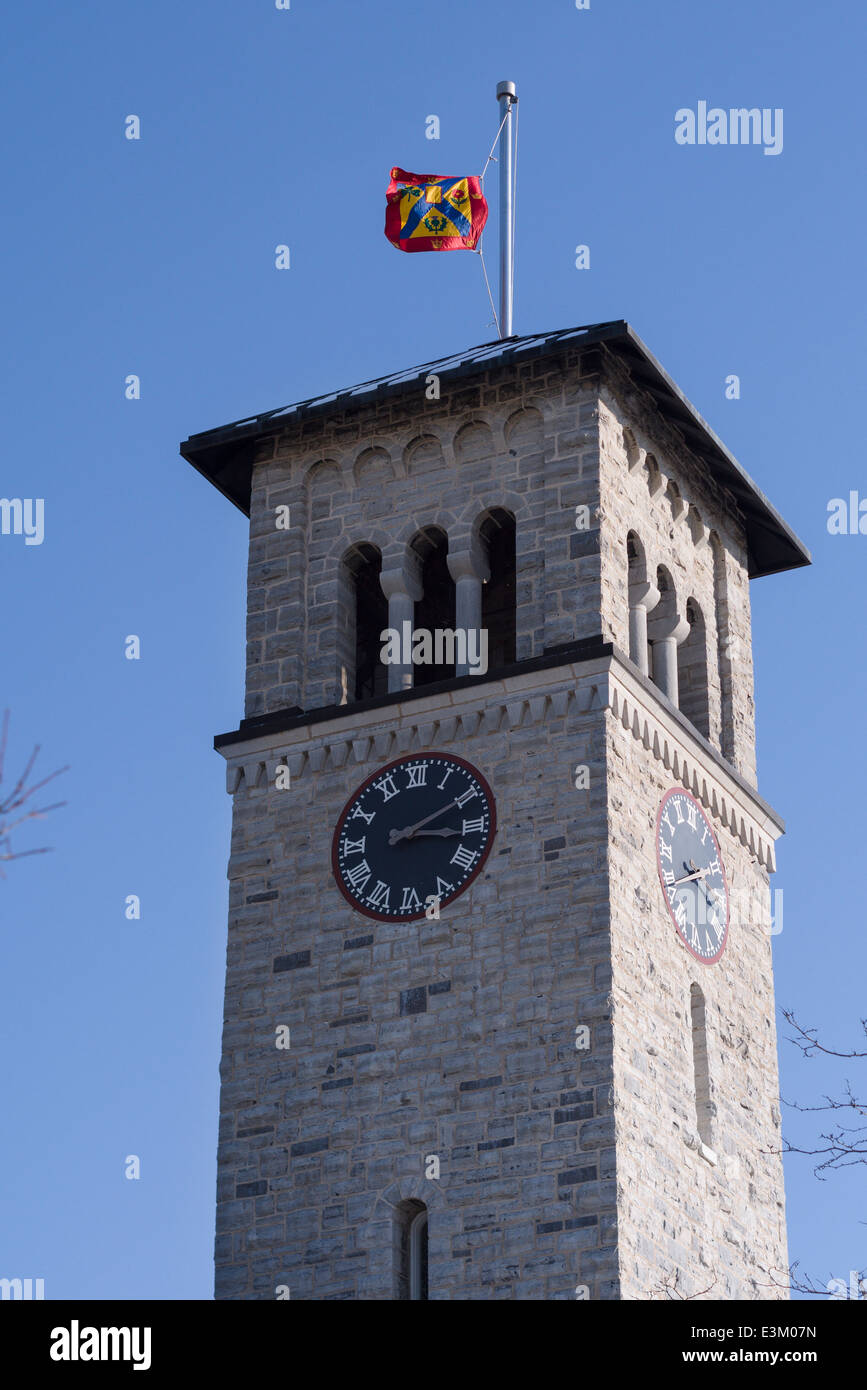 Grant Hall clock tower at with Queen's University Banner. The limestone clock tower is a campus icon. The university - Stock Image