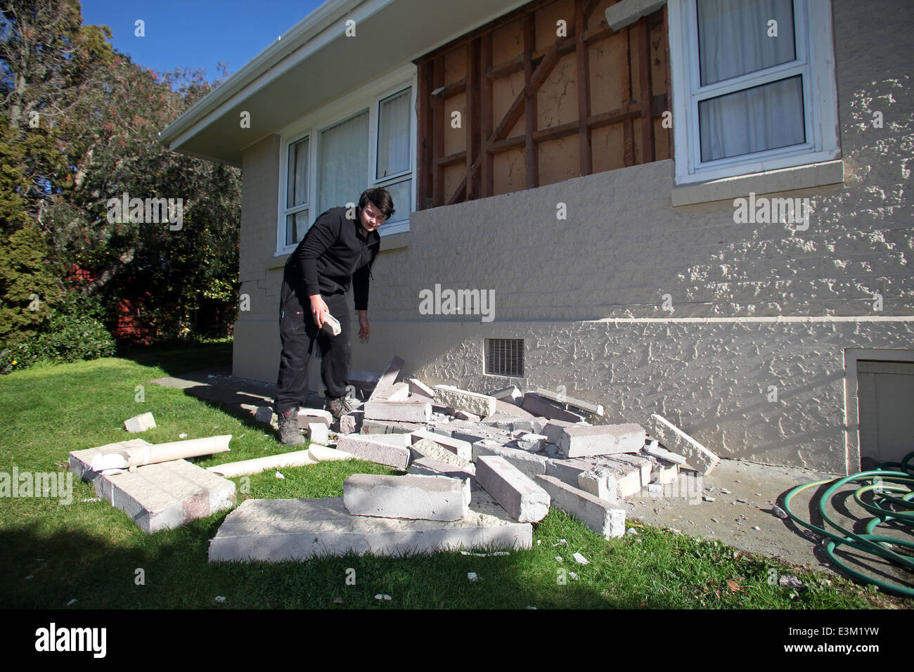 A man tidies after the July 2013 earthquake that struck close to Seddon brought part of his wall down, Marlborough, - Stock Image