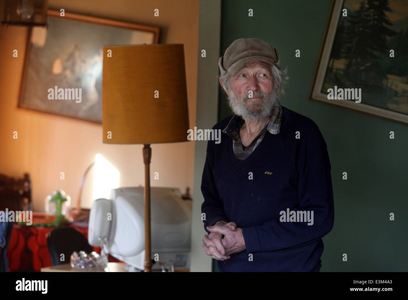 A man whose house suffered badly from the July 2013 earthquake in Seddon, New Zealand, in his lounge. - Stock Image