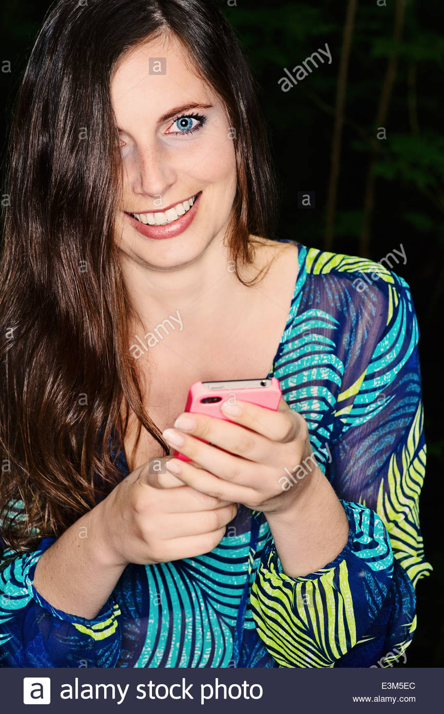 Young woman with long brown hair holding her phone in hand,Junge Frau mit langen braunen Haaren hält ihr Telefon - Stock Image