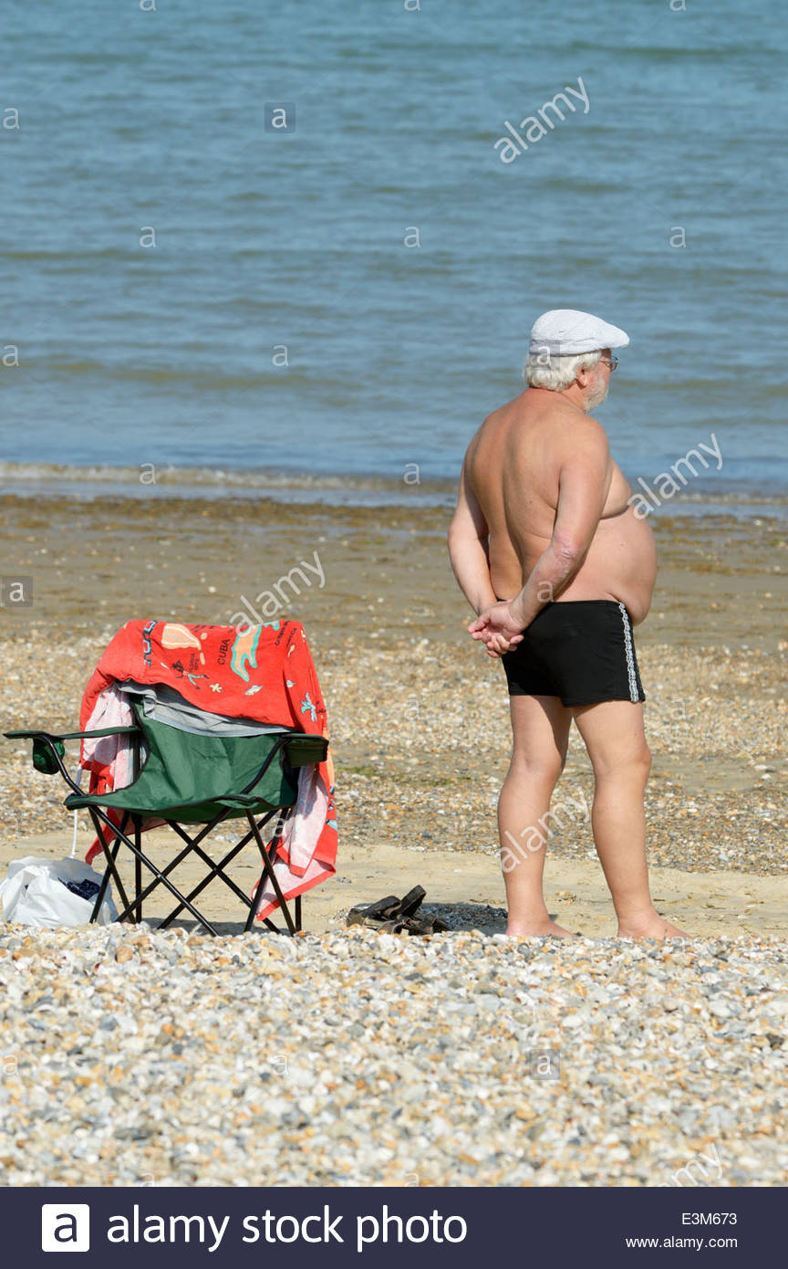 Overweight older man in swimming trunks stood on the beach in the sunshine  at Weymouth,