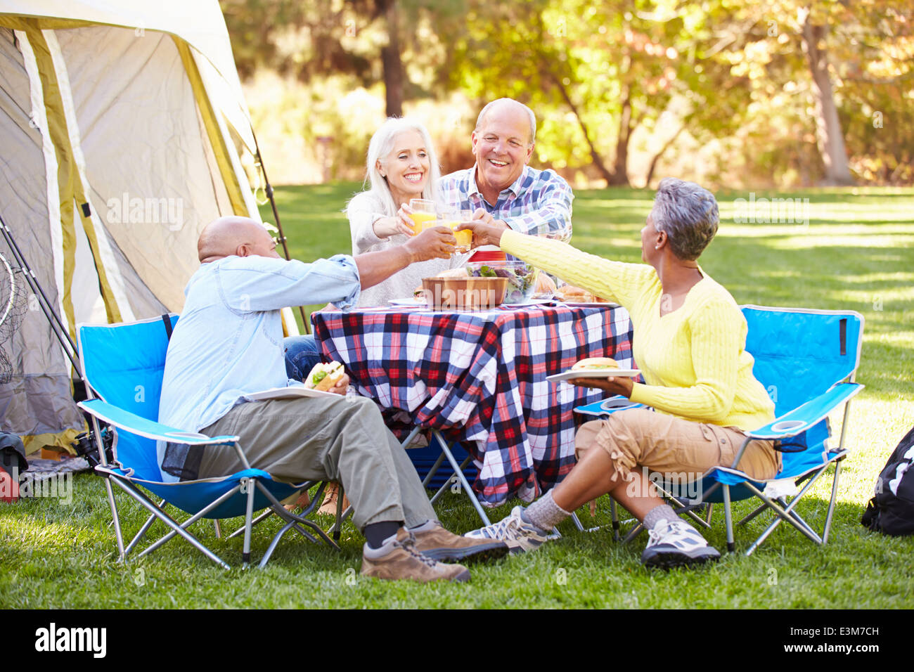 Two Senior Couples Enjoying Camping Holiday In Countryside Stock Photo