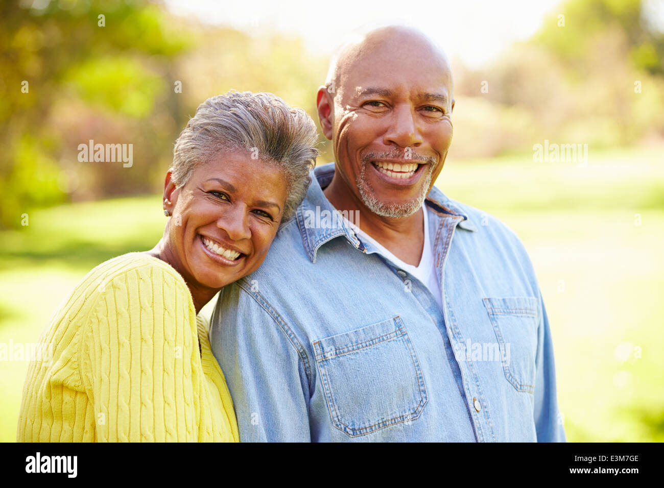 Senior Couple Walking Through Autumn Woodland - Stock Image