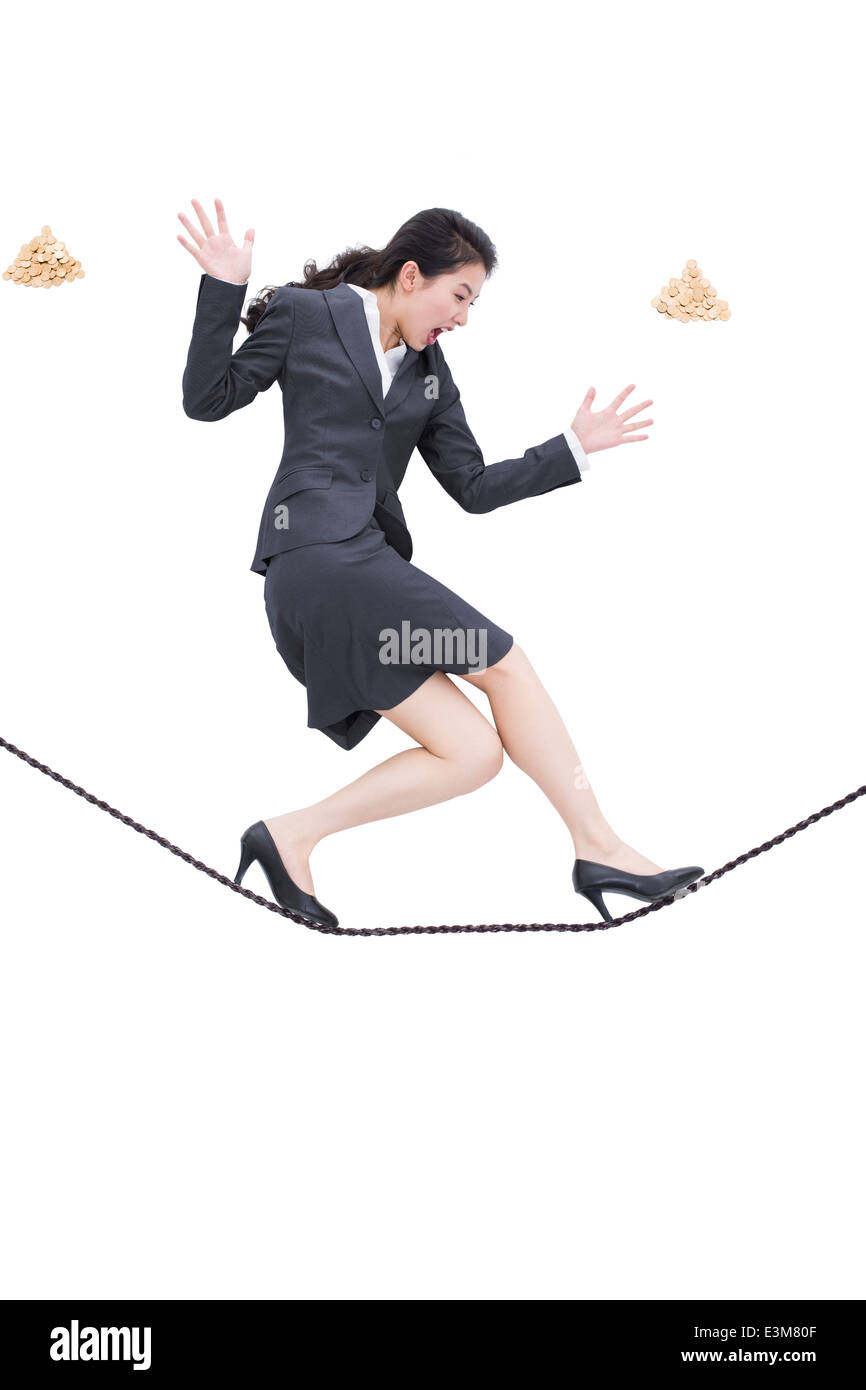 Businesswoman walking on rope - Stock Image