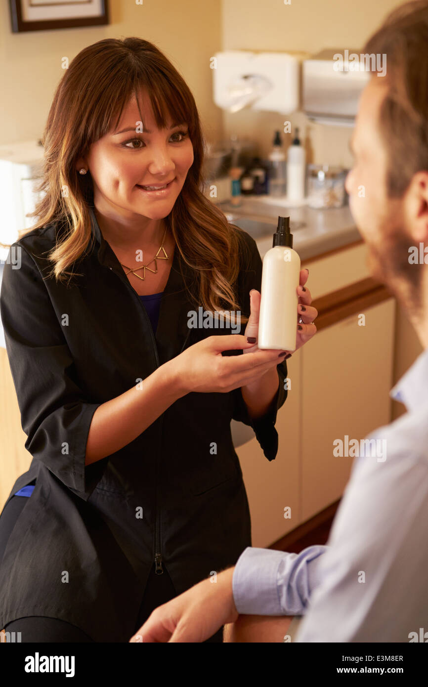 Beautician Advising Male Client On Beauty Products - Stock Image