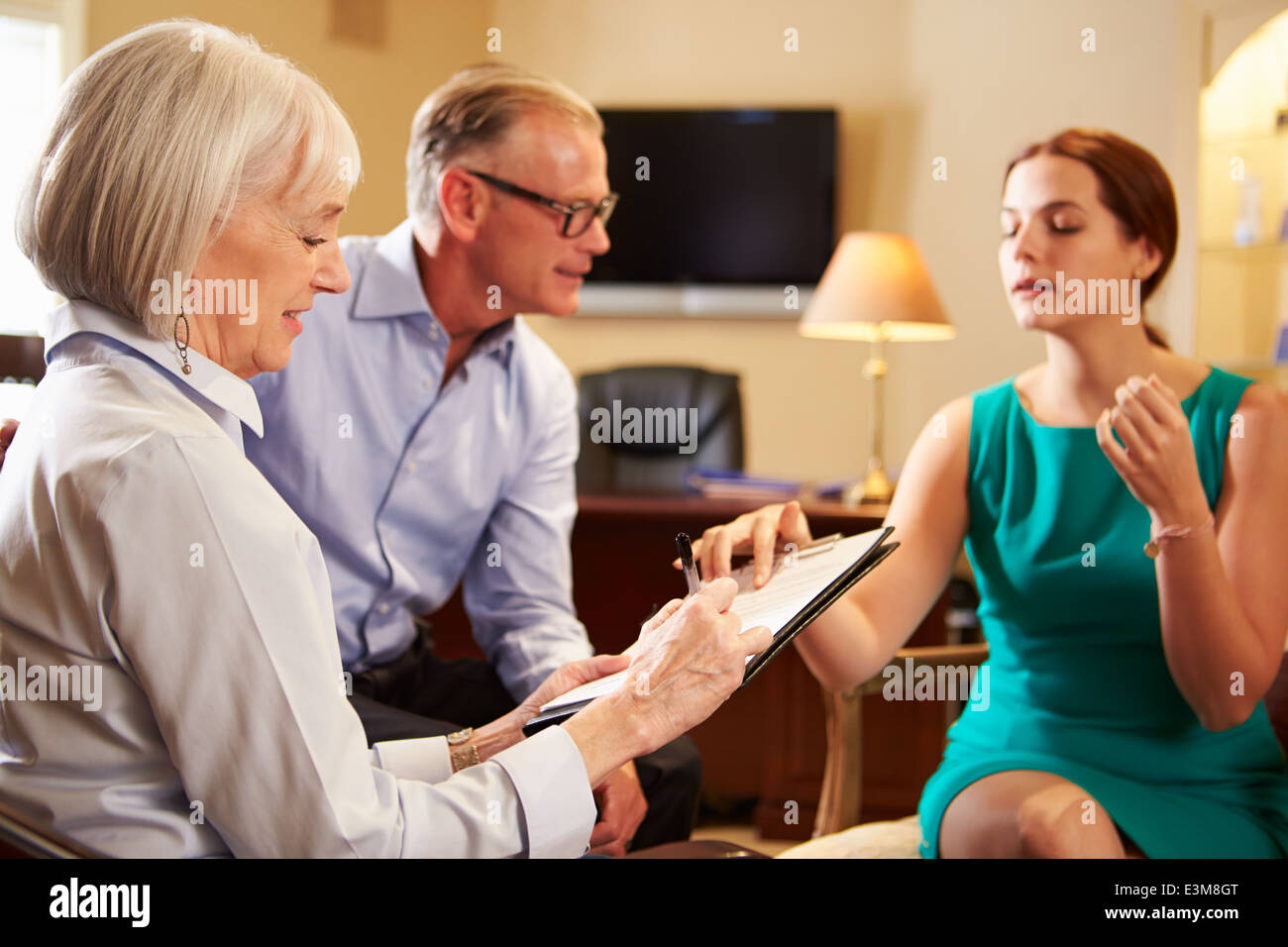 Older Couple Talking To Financial Advisor In Office - Stock Image