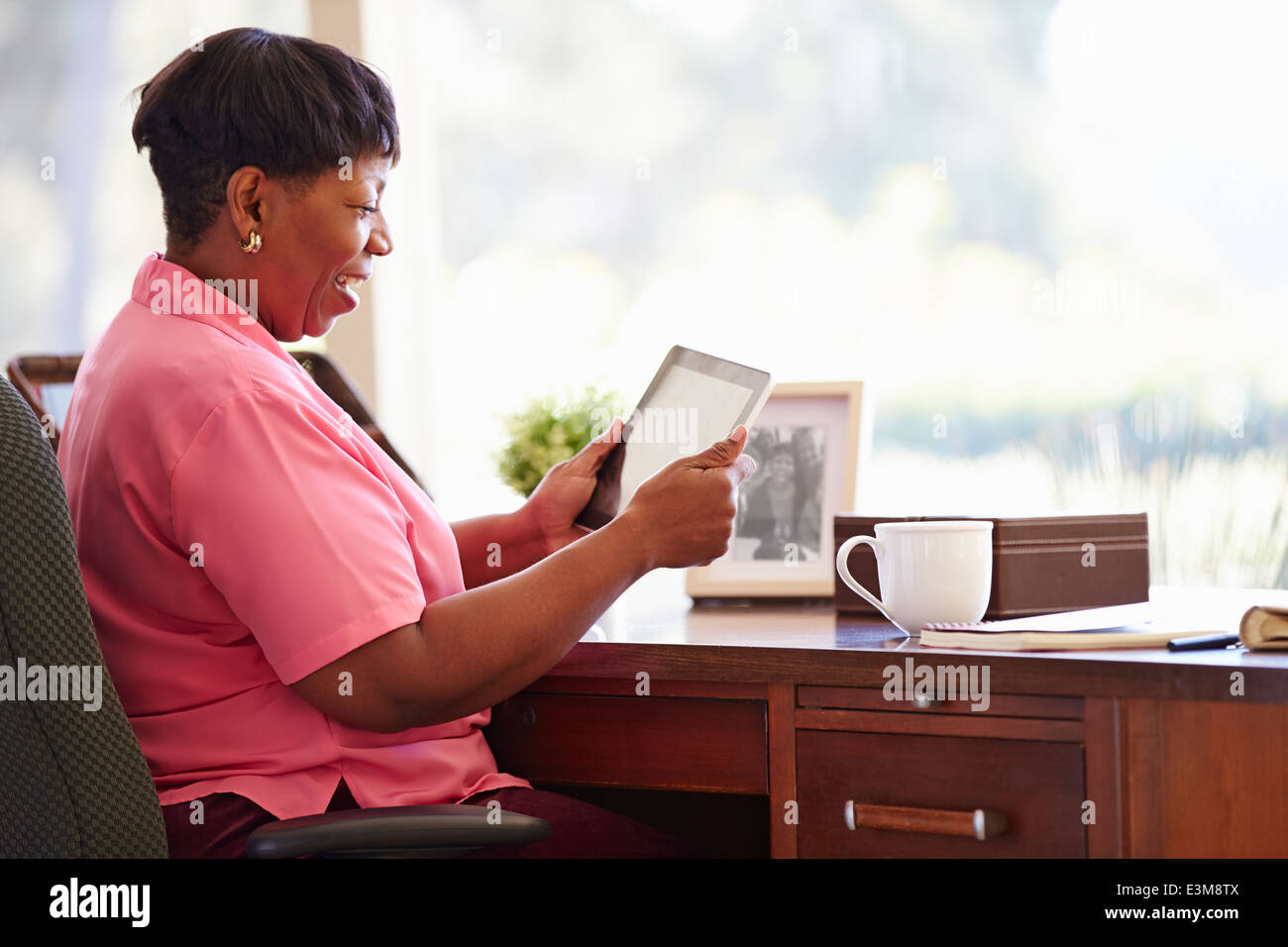 Mature Woman Using Digital Tablet On Desk At Home - Stock Image