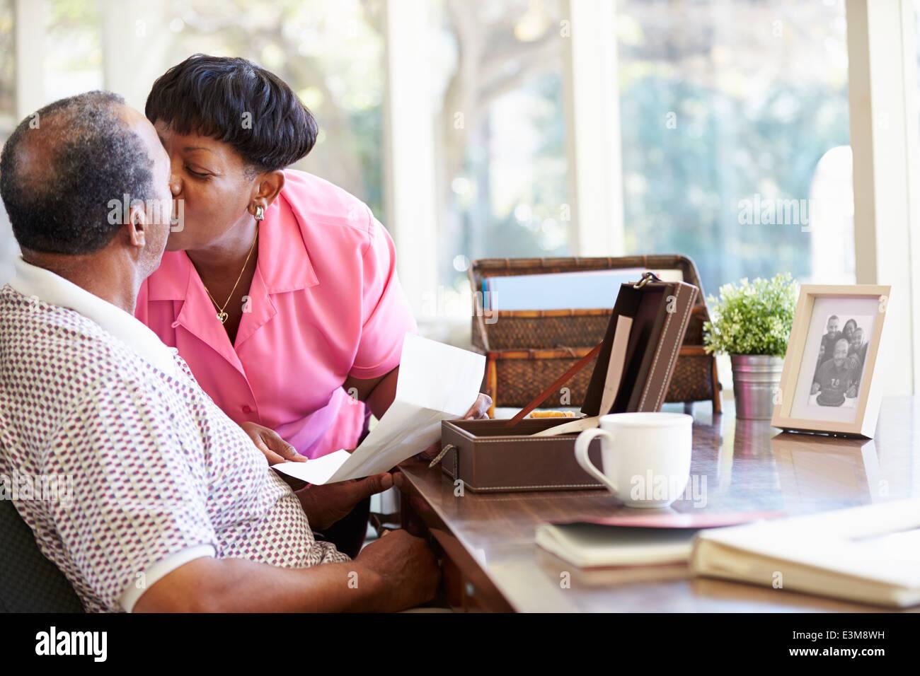 Senior Couple Putting Letter Into Keepsake Box - Stock Image