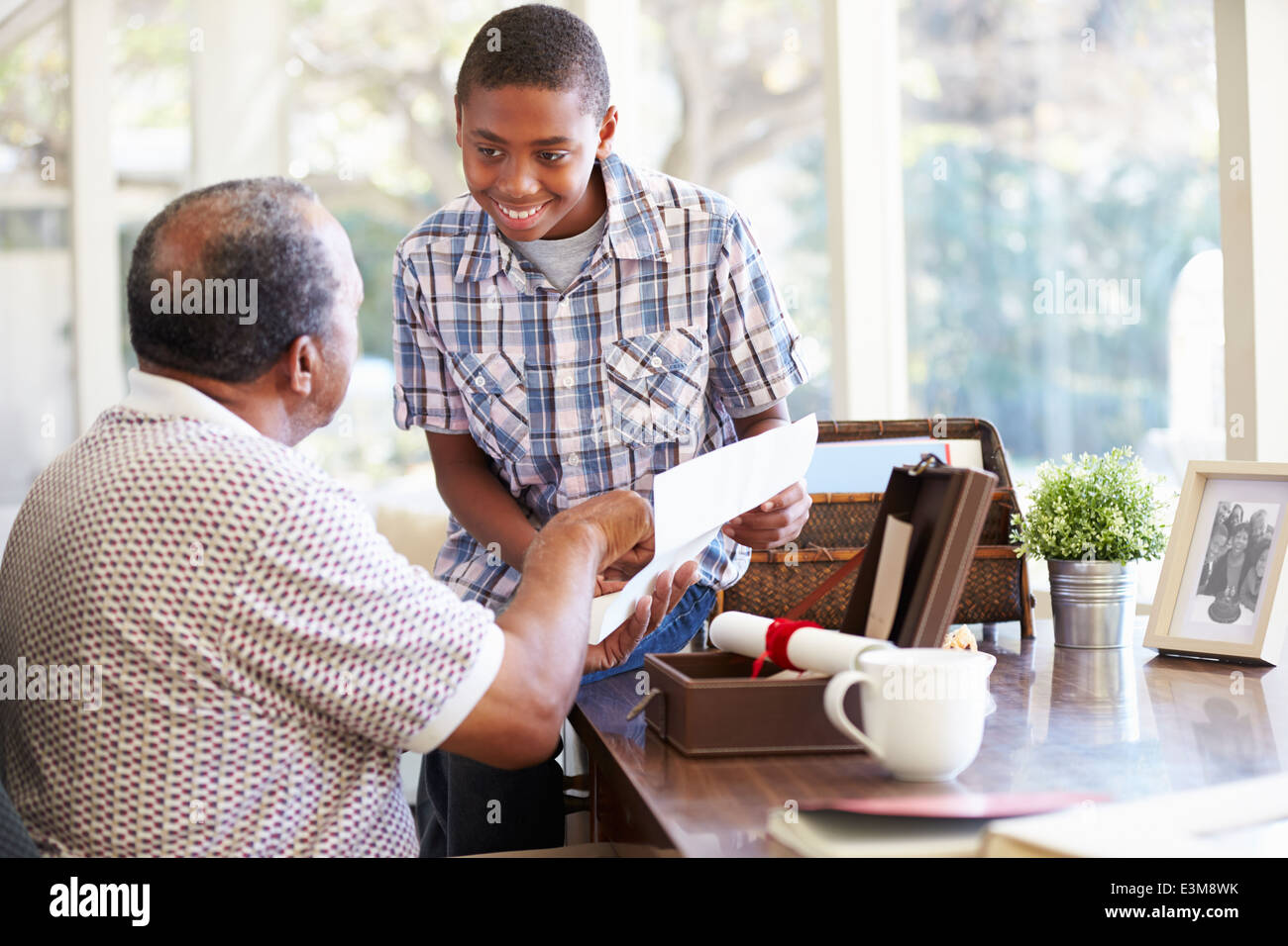 Grandfather Showing Document To Grandson - Stock Image