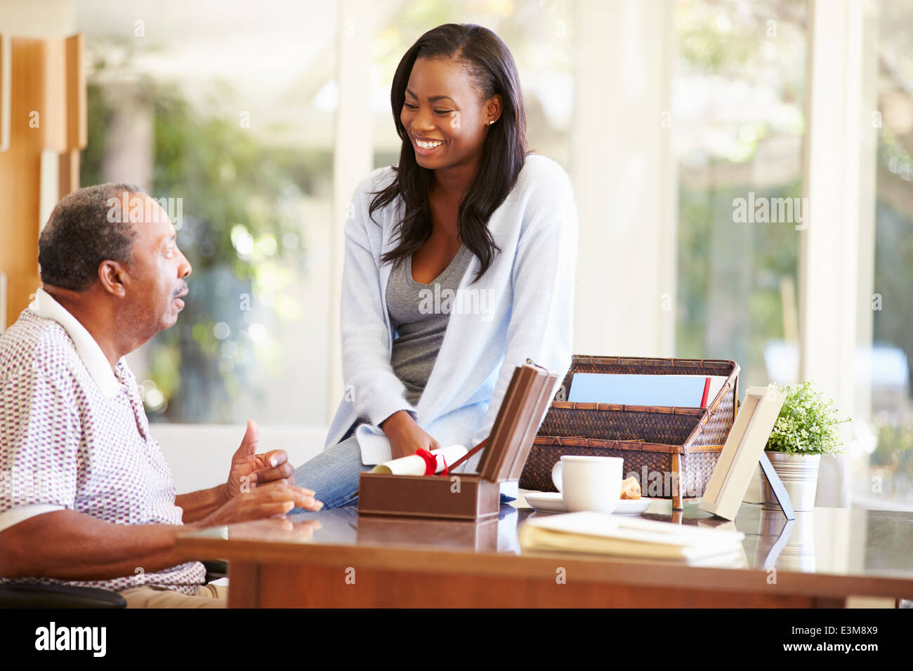 Senior Father Discussing Document With Adult Daughter - Stock Image