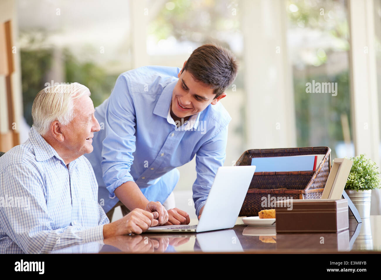 Teenage Grandson Helping Grandfather With Laptop - Stock Image