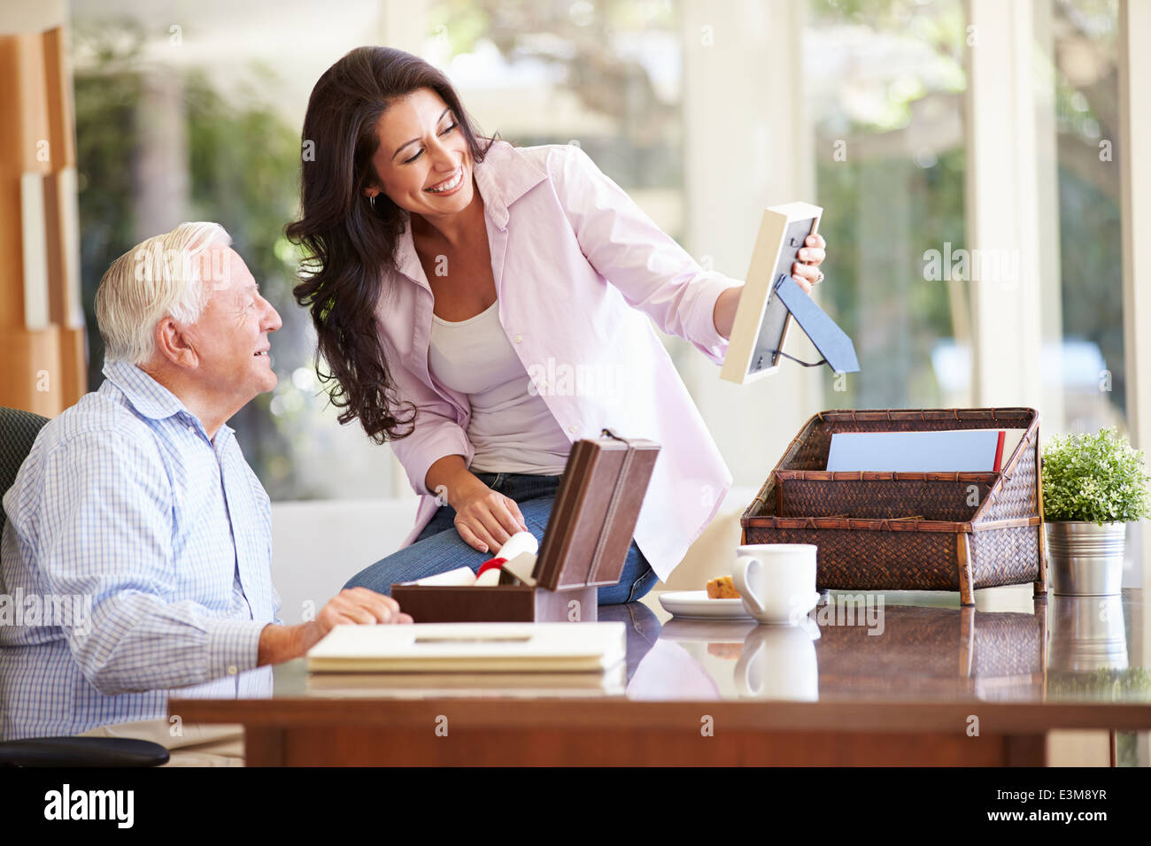 Senior Father Looking At Photo In Frame With Adult Daughter - Stock Image