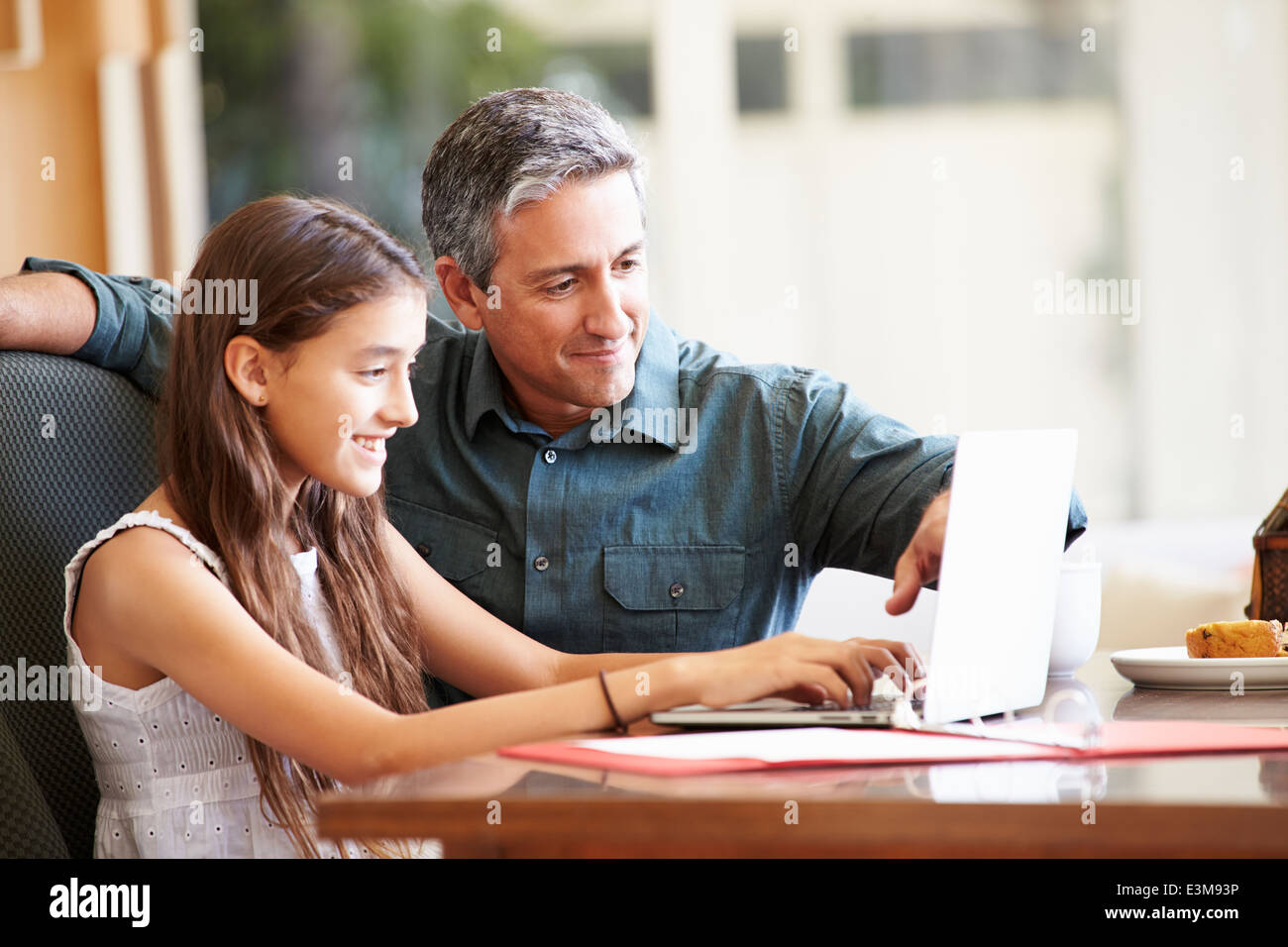 Father And Teenage Daughter Looking At Laptop Together - Stock Image