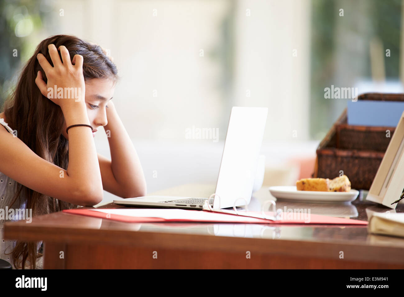 Stressed Teenage Girl Using Laptop On Desk At Home - Stock Image