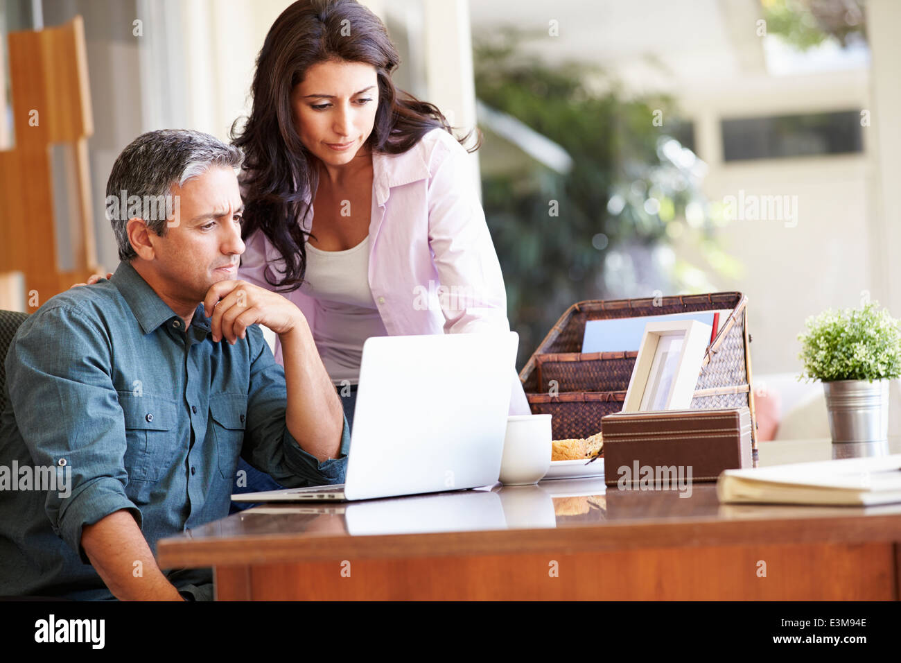 Worried Hispanic Couple Using Laptop On Desk At Home - Stock Image