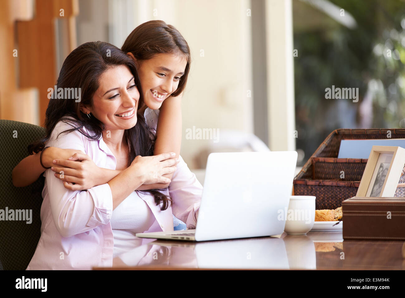 Mother And Teenage Daughter Looking At Laptop Together - Stock Image