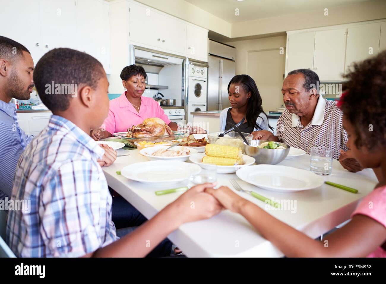 Multi-Generation Family Saying Prayer Before Eating Meal - Stock Image