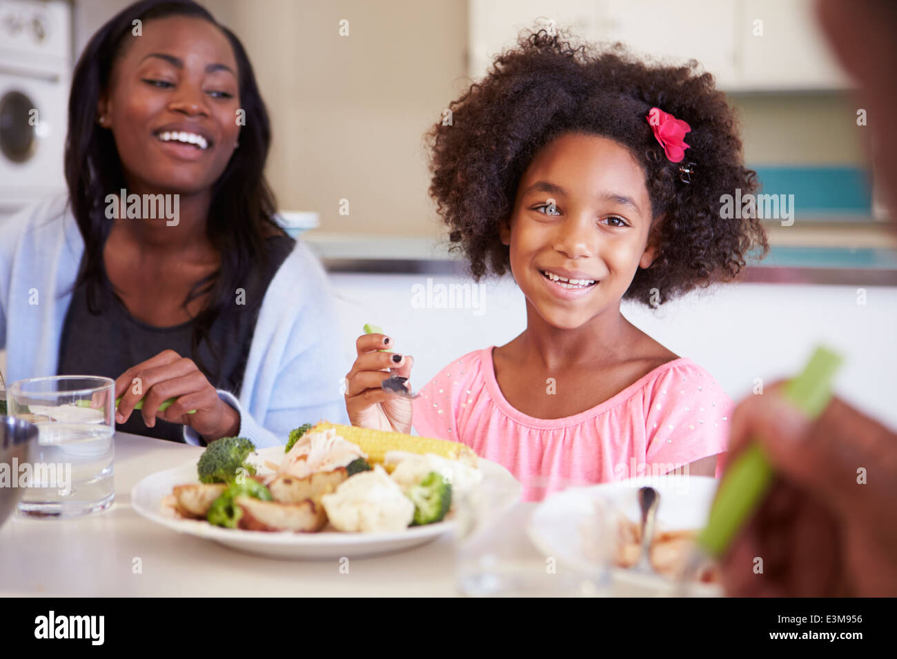 Mother And Daughter Having Family Meal At Table - Stock Image