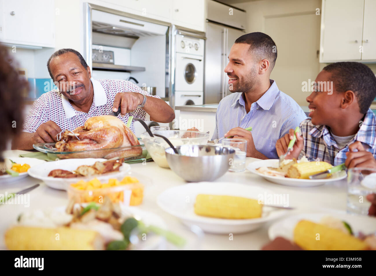 Multi-Generation Family Sitting Around Table Eating Meal - Stock Image