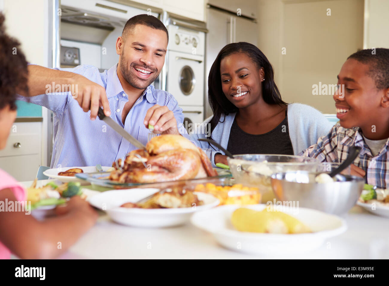 Family Sitting Around Table At Home Eating Meal - Stock Image