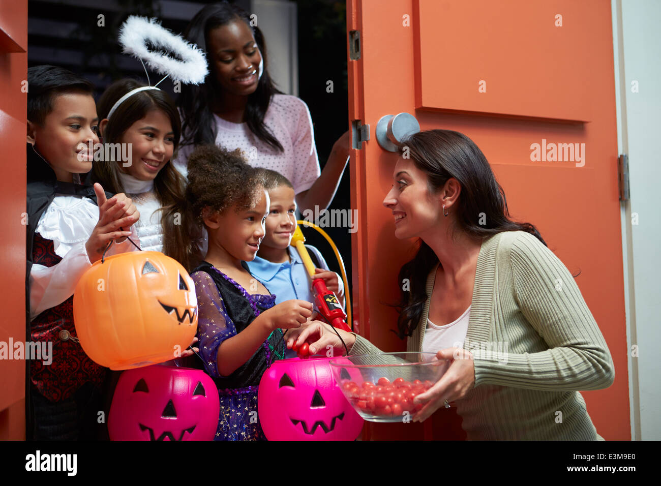 Children Going Trick Or Treating With Mother - Stock Image